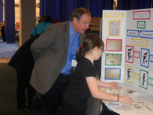 Mike Hirtle looking at a child's poster during the Young Inventor challenge