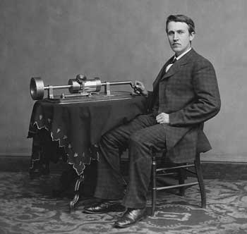 Black and white photo of male Inventor sitting by invention