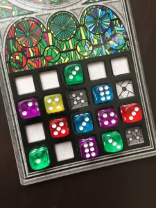 Sagrada game dice in a player board multi colored dice with pips in a grid